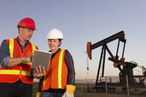 A royalty free image from the oil and gas industry of a male and female oil worker using a tablet computer in front of a pumpjack